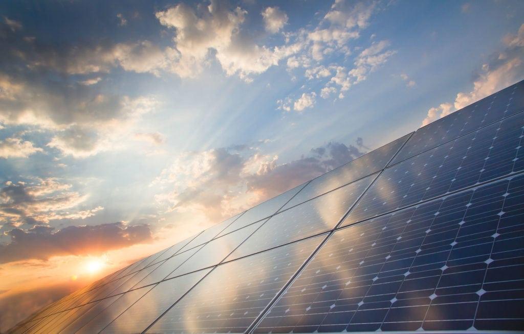Photovoltaik-Fläche bei Sonnenschein mit einzelnen Wolken am Himmel